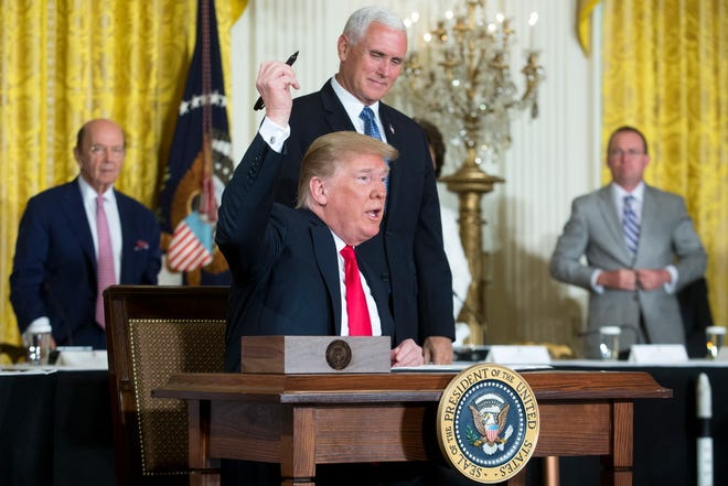 President Donald Trump signs an executive order to establish a Space Force, with Vice President Mike Pence.