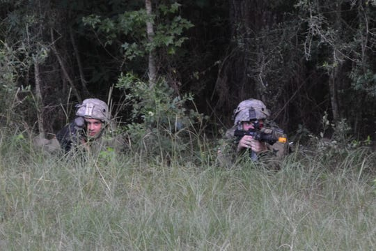 Specialist Michael Smilie (at right) and E1 Michael Rodriguez take a cover position while infantry soldiers from 3rd Battalion, Bravo Company practice crossing an open road during the XCTC training exercises at Camp Shelby, Miss.