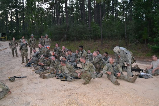 Infantry soldiers with the La. National Guard 3rd Battalion, Bravo Company, listen as leaders review their performance after a mission during XCTC training at Camp Shelby, Miss.
