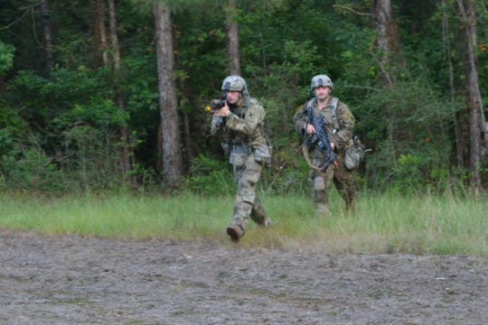 Infantry soldiers Spc. Guidry (left) and PFC. Chandler Richey with 3rd Battalion, Bravo Company, of the La. National Guard cross a roadway during a training session at Camp Shelby, Miss.