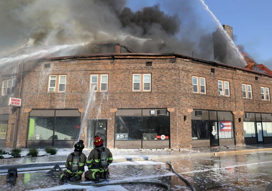 Firefighters direct water onto the Brin Building as it burns in downtown Menasha on Aug. 10, 2018.