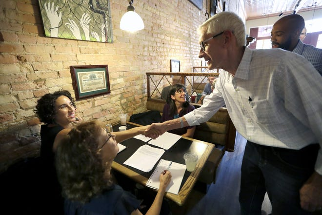 Democratic gubernatorial nominee Tony Evers shakes hands with Meredith Mason of Appleton as he visits customers with Lt. Gov.  nominee Mandela Barnes, back right, at the Copper Rock Coffee Co. in downtown Appleton.