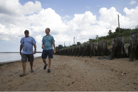 Vic Simon, commodore of Sandy Hook Bay Catamaran Club and Benson Chiles  walk along the water on the land in question.