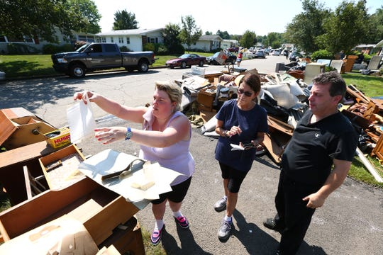 Jennifer Brincat, l, Noreen Reinhart and Patrick Brincat sort through Jennifers grandmother and Noreen's mother's damaged photo albums in the Greenbriar age-restricted Senior community, a neighborhood that was completely flooded with 3 feet of water. The water receded at 5am the day after the storm but over 100 houses were damaged.  August 15, 2017, Brick, NJ.