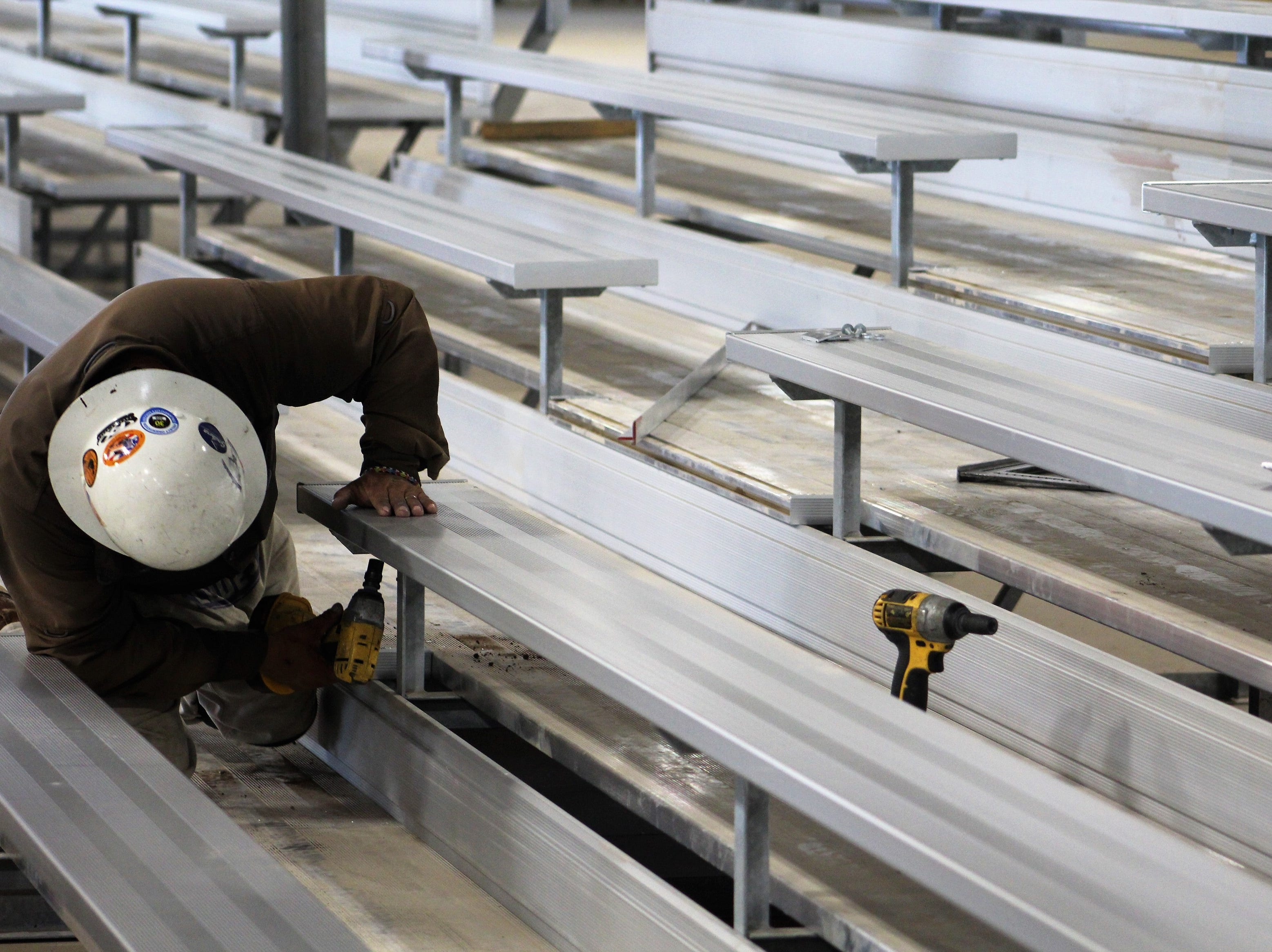 A worker secures bleacher seats Wednesday inside the new livestock barn at the Taylor County Expo Center. Metal used in the structure that is equivalent to two football fields was purchased in 2017, before prices rose. The facility will be ready for livestock shows at September's West Texas Fair & Rodeo.