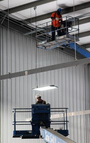 Lifts take workers to the ceiling of the new livestock barn at the Taylor County Expo Center. The facility is the size of two football fields placed end to end. A certificate of occupancy could be issued as early as next week.