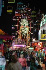 The Seattle Wheel acts as a backdrop for the midway at the NC Mountain State Fair in 2017.