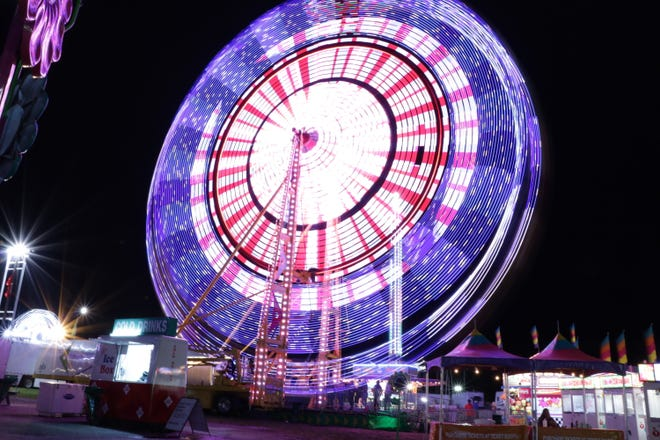 The Seattle Wheel at the Mountain State Fair as it lights up the September night.