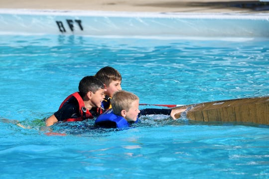 Noah Gregory, 7, Wylan Doty, 10, and Jasper Tate, 7, swim their cardboard boat to the side of the Malvern Hills pool after sinking during AshevilleÕs Inaugural Cardboard Regatta held by Asheville Parks and Recreation at the Malvern Hills pool on Friday, Aug. 10, 2018.