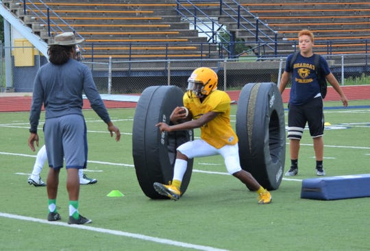 Battle Creek Central running backs go through a drill, trying to avoid to large tires, during a preseason practice this week.