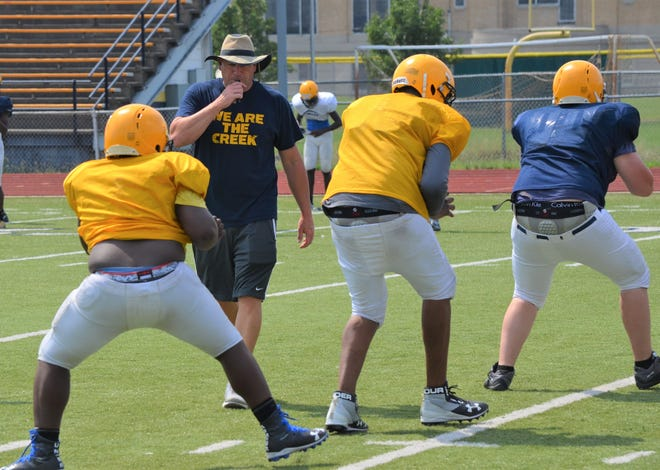 BCC head coach Lorin Granger works with the offensive line on a blocking drill during preseason practice this week.
