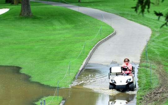 A volunteer drives a golf cart through water near the 15th fairway at En-Joie Golf Course in Endicott on Wednesday, August 15, 2018. The first round of the Dick's Sporting Goods Open is scheduled for Friday.