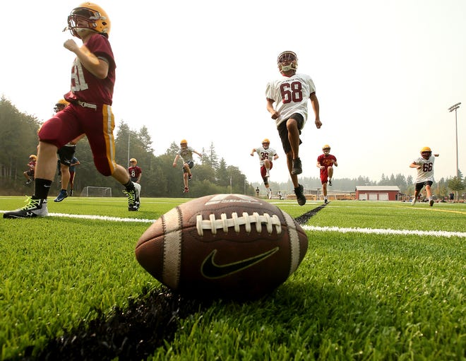 Kingston High School football players warm up on the first day of practice on Wednesday. Among area schools, only Kingston and North Kitsap practiced outside on Wednesday. Other teams were driven inside due to poor air quality.