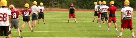 Kingston High football coach Alec Grimm works with his team during their first practice of the season on Wednesday.