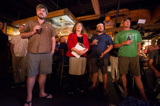 Derek Hallquist, left, with parent Christine Hallquist and supporters watch a video during her victory speech during the Primary party for the Democratic candidate for governor at the Skinny Pancake on Tuesday night August 14, 2018 in Burlington.