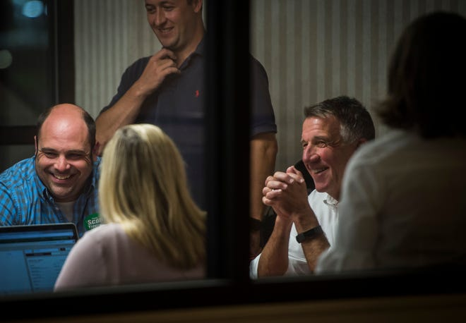 Right, Gov. Phil Scott cracks a smile in his campaign war room at the Comfort Inn & Suites in Berlin after returns indicate that he won the Republican primary Tuesday night, Aug. 14, 2018. Dustin Degree, who works in the Scott administration as special assistant to the governor and executive director of workforce expansion, sits to the left.