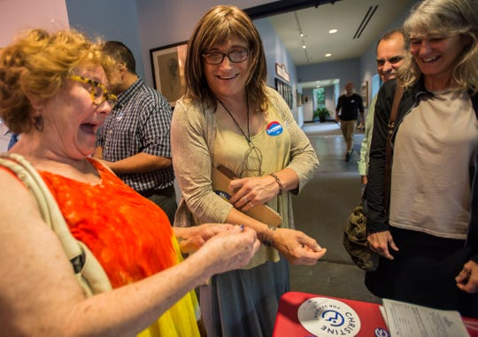 Center, Vermont democratic gubernatorial candidate Christine Hallquist hands out campaign buttons at a unity rally in Burlington, Vt., on Wednesday night, Aug. 15, 2018, a day after she made US election history as the first transgender woman to win a major party primary for governor.