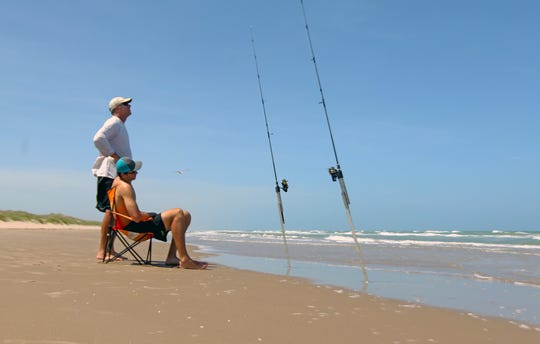 At the end of a long day, Luke McGhee and his dad, Steve, relax beside a couple of baited rods on Padre Island National Seashore.