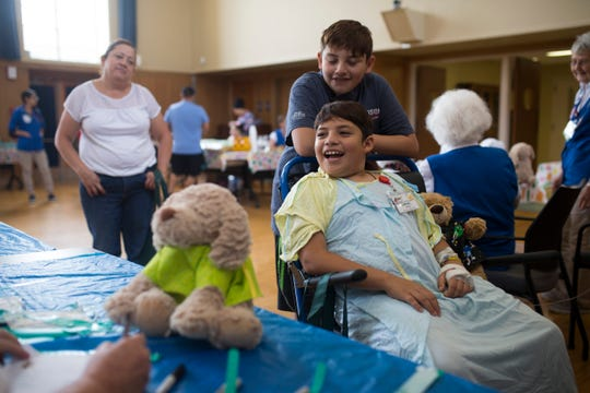Samuel Martinez (bottom) and his brother Nathanel Martinez help their bear get treatment during the Teddy Bear Hospital event organized by the Stripes Child Life Program on Wednesday, Aug. 15, 2018 at Driscoll Children's Hospital.