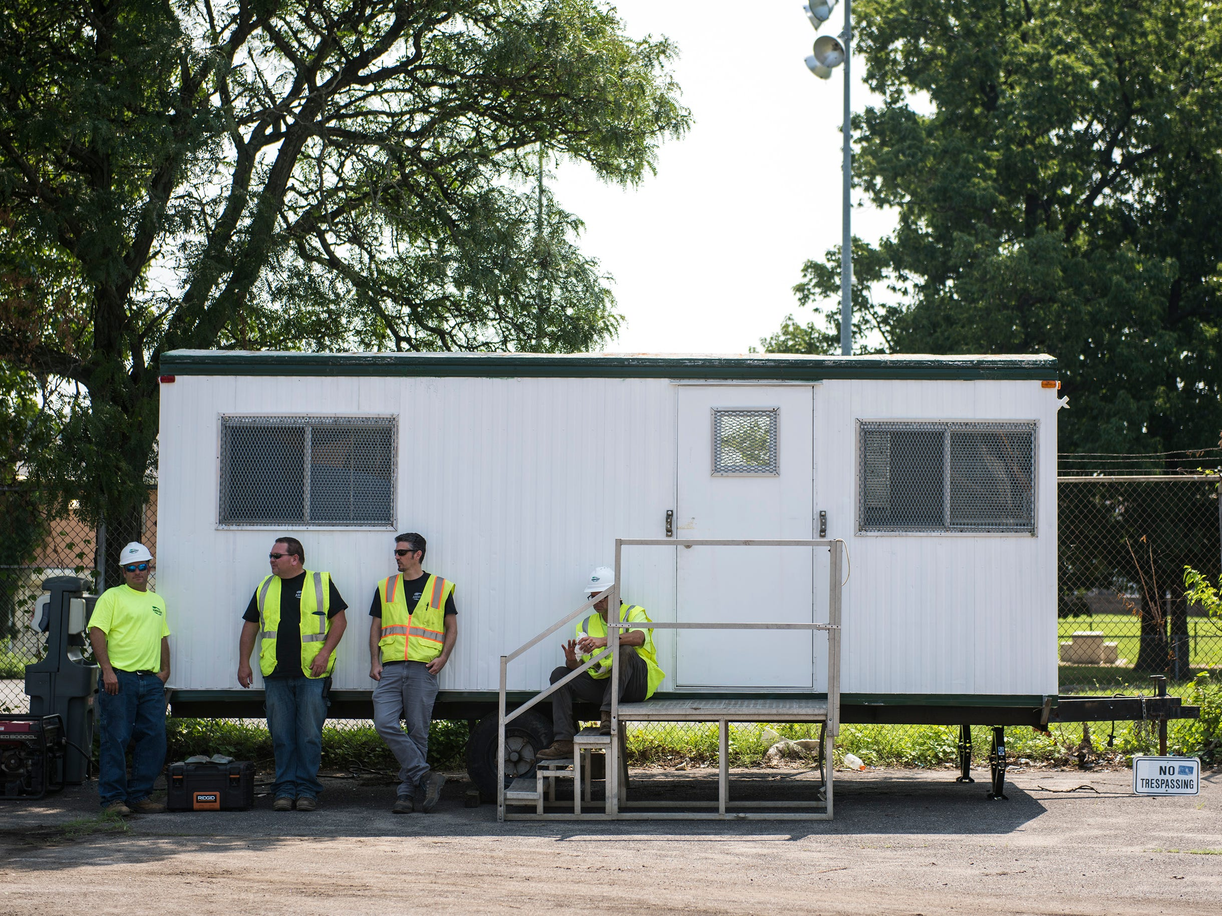 A crew stands by as a press conference is held at the Camden Labs site Wednesday, Aug. 15, 2018 in Camden, N.J. The former toxic and illegal dumping site will be cleaned and cleared to make way for recreational open space.