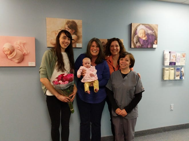 Midwives Deirdre Horvath, CNM, APN-C (left), Catherine McCabe, CNM, APN-C (near right), and Barbara Labrie, CNM (right) pose with mom Cindy Harris and her daughter Joanna, the 5000th baby delivered by the midwives at All Women's Healthcare in Flemington