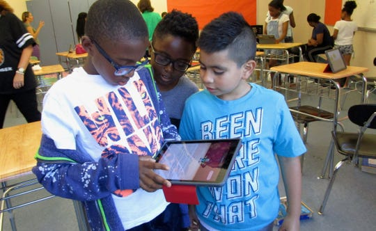 Malachi Mytil (going into fifth-grade at School No. 4), David Kahiga (Grade 3, School No. 4), Henry Zuniga (Grade 3, School No. 2) use an Apple iPad to code the Meebot robot during a summer coding camp for elementary school students at Linden Public Schools' Academy of Science and Technology.