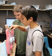 "7th graders Colin Foley (left) and Gregory Simpson combine polystyrene, robotic programming software and lots of imagination in Daniel Black's ""Animatronics & Intro to Robotics"" class at STEM Camp, offered each summer by the Westfield Public School District."