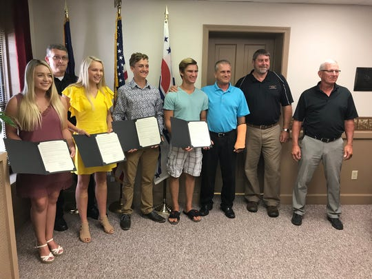 Lifeguards Makenzie Hudson, Carolyn Cox, Andrew Martin and Caleb Fischer were honored by Coshocton County Commissioners Gary Fischer, D. Curtis Lee and Dane Shryock and EMS Director Todd Shroyer, rear, for saving the life of Jordan Washington recently at the River View Community Pool.