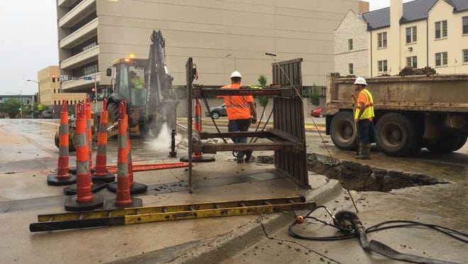Des Moines Water Works crews hammer Park Street during a water outage in the area.