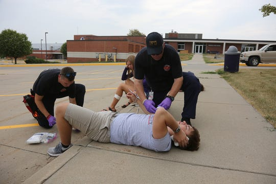 Indianola High School student Doug Voigts gets attention from Indianola firefighters while playing a victim in an active-shooter training in August at Indianola High School.