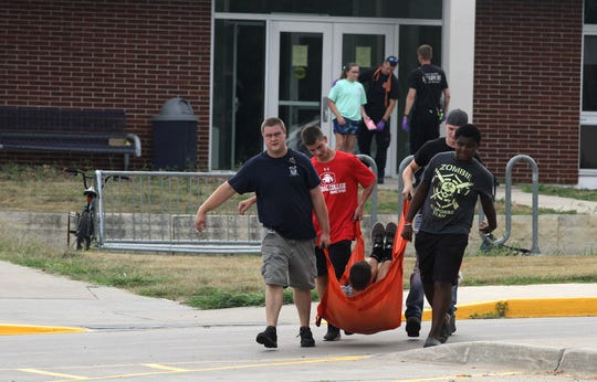 An Indianola firefighter and student volunteers carry a student who is playing a victim of an active shooter during a training exercise in August at Indianola High School.