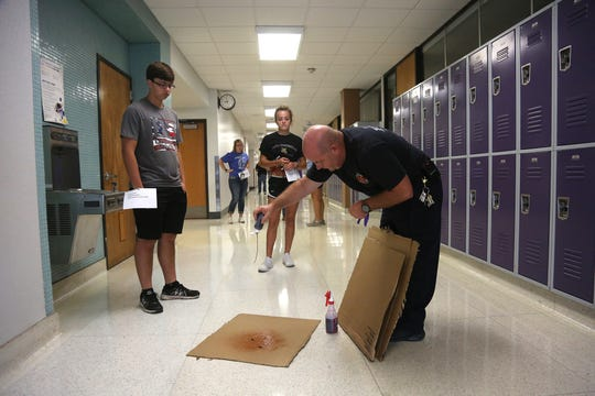 Indianola Fire Department paramedic Chuck Cross sprinkles fake blood onto a cardboard sheet while Indianola High School students set to act as victims watch. The Indianola police and fire departments along with the Indianola Community School District and other law enforcement and first responder agencies conducted active shooter training at Indianola High School on Aug. 14.
