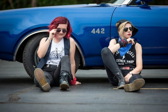 Katie Larson (left) and Sav Buist of the Accidentals posing in front of a restored 1969 Oldsmobile Cutlass.