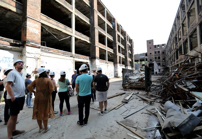 People look around at the scope of the buildings as a tour guide gives them historical information, during the Pure Detroit tour, in partnership with Arte Express, of the Albert Kahn Associates designed Packard Automotive Plant in Detroit on Saturday, Aug. 12, 2018.