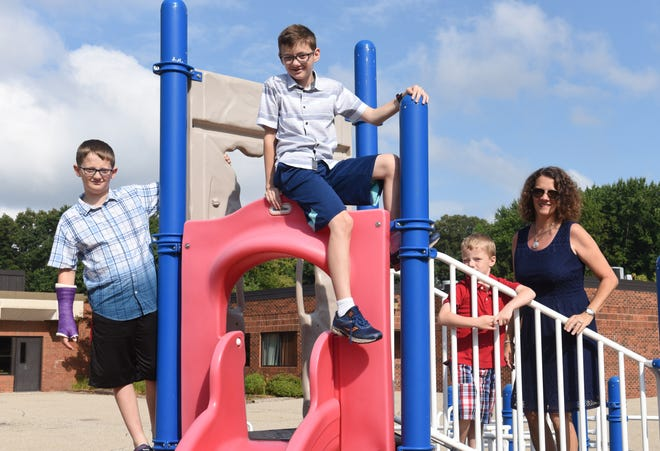 Nancy Bush, of Shelby Township, with her three sons (from left) Christian, 12, Graydon, 12, and Benjamin, 5, at the playground at Crissman Elementary School in Shelby Township. Bush wants Utica schools to push back the time that middle and high school starts in the district.