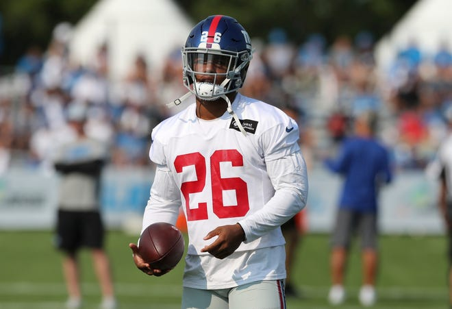 New York Giants running back Saquon Barkley walks through a drill on the field during the joint practice with the Detroit Lions on Tuesday.