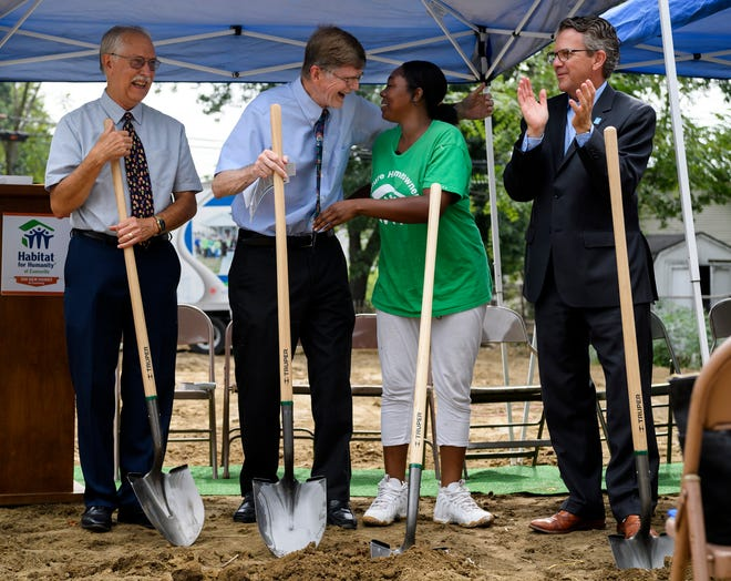 Future homeowner Tamisha Dilworth, center right, receives a congratulatory hug from Dennis Davenport, center left, before they break ground on the 500th Habitat for Humanity house with Joe Easley, left, Mayor Lloyd Winnecke, right, and other community members in Evansville's Ballard Neighborhood, Wednesday, Aug. 15, 2018. Habitat for Humanity plans to have the house built by the end of the year.