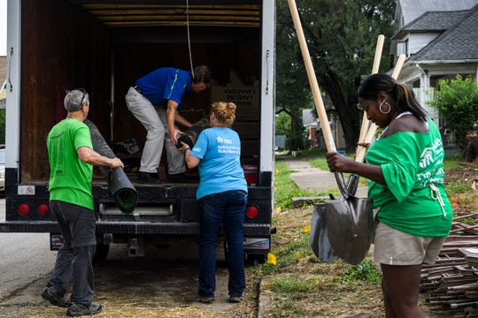 Habitat for Humanity workers load up chairs, shovels and supplies that were used during the groundbreaking ceremony for the organization's 500th house in Evansville's Ballard Neighborhood, Wednesday morning, Aug. 15, 2018. Lisa Boyd-Davis, right, attended the ceremony, which honored her friend and future neighbor Tamisha Dilworth, not pictured, before checking out the progress on her own house located across the street.