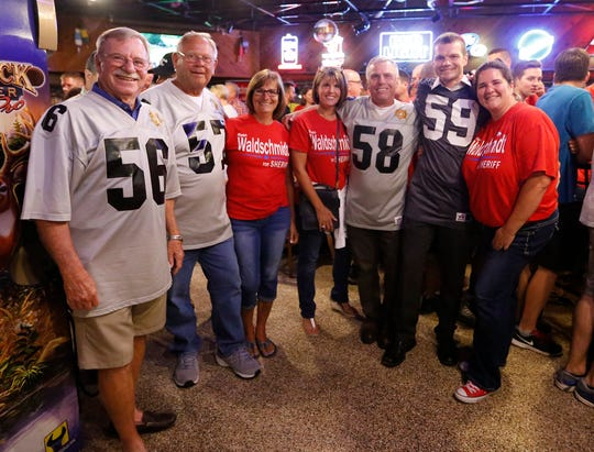 Fond du Lac County Sheriff elect Ryan Waldschmidt (second from right) poses with (left to right) former sheriffs Jim Gilmore and Gary Pucker, Vickie Pucker, Mickie Fink; Sheriff Mick Fink, Waldschmidt and his wife, Sara. The group were gathered with jerseys indicating which Fond du Lac County Sheriff each was/is with Waldschmidt supporters Tuesday at Schmitty's Oar House in Fond du Lac to celebrate the primary election victory of Waldschmidt for Fond du Lac County Sheriff.