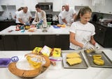 Volunteers from UBS make dinner for residents of the Ronald McDonald house in Fort Myers. The dinners give families a hot meal.