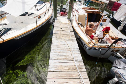 Dave Miller, a three-year live-aboard resident of Paradise Marina in North Fort Myers, takes an outdoor shower on his sailboat on Wednesday, Aug. 15, 2018. The marina has been one of the hardest hit areas from the blue-green algae blooms. Congressman Francis Rooney made a visit to talk water quality issues in Southwest Florida.