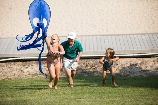 """August Wisniewski, left, works to get an octopus kite to set sail with help from her grandfather, Tom Wavernek, and sister Olive Wisniewski at last year's """"Soar on the Shore"""" in Algoma. This year's kite festival on Crescent Beach takes place Aug. 18."""