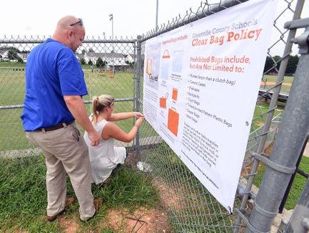 Riverside High School athletic director Murray Long and intern Abby Aycock hang a Clear Bag Policy sign outside the football stadium at the school in Greer Wednesday.