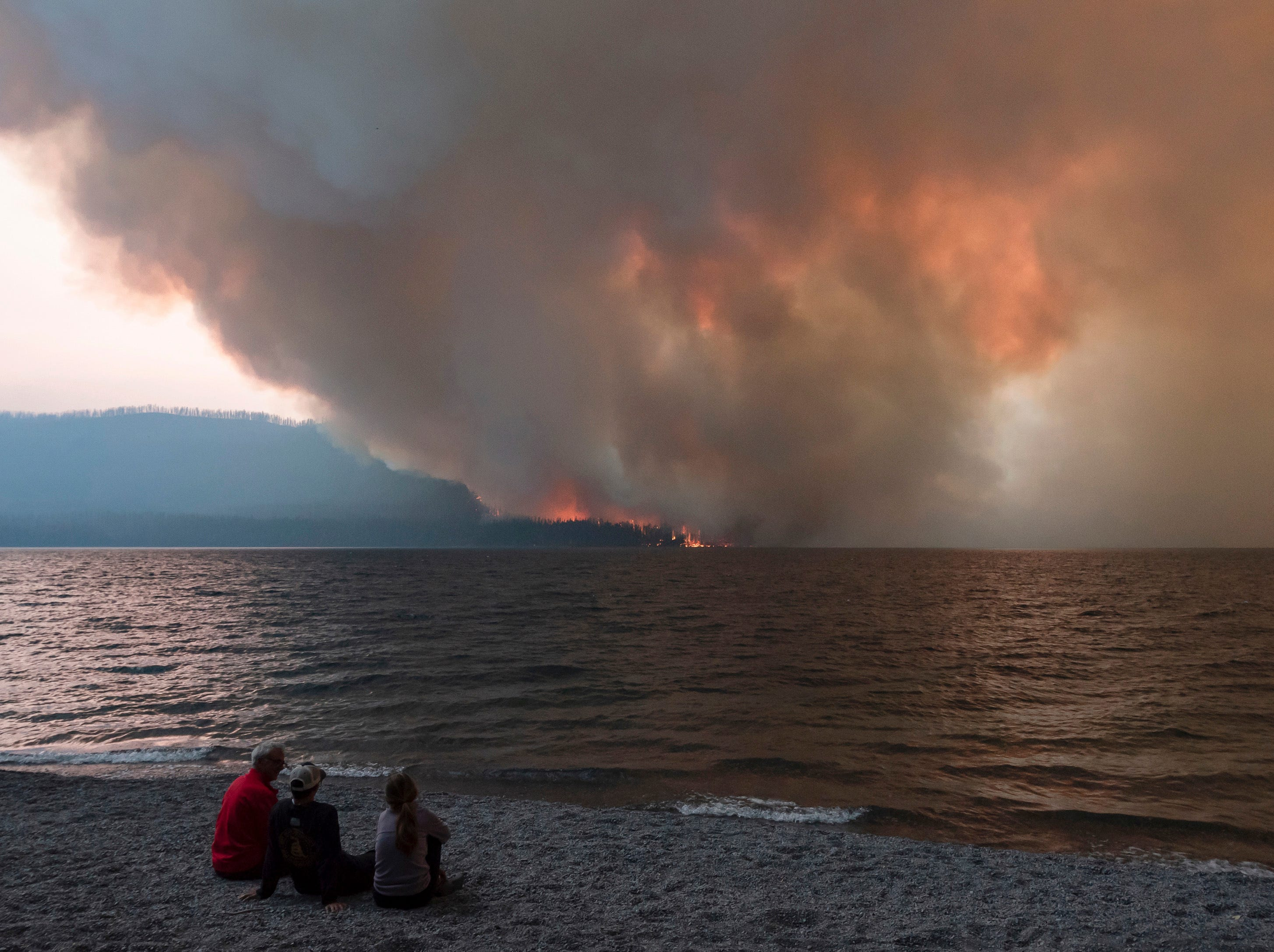 In this Sunday, Aug. 12, 2018, the Howe Ridge Fire burns at Glacier National Park, Mont. At least nine homes and cabins in a historic district of Glacier National Park have been destroyed in a wildfire that raged through the Montana park's busiest area and prompted the hasty evacuation of hundreds of visitors. Park officials said Tuesday, Aug. 14, 2018, that the lost buildings include the so-called Big House at Kelly's Camp, a resort developed early last century serving auto travelers along Glacier's famous Going-to-the-Sun Road. (Kristy Pancoast via AP)