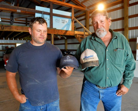Cameron Poncelet, left, and his father Jeff compare hats that show the change in company logo as the Poncelet family business passes to its 4th generation.