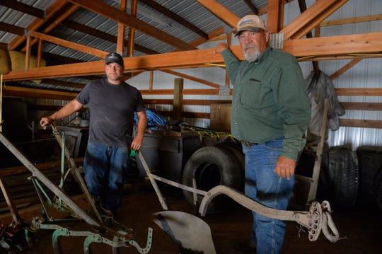 Jeff Poncelet, right, and his son Cameron with some of the farm implements from four generations ago when the family business was a truck garden.