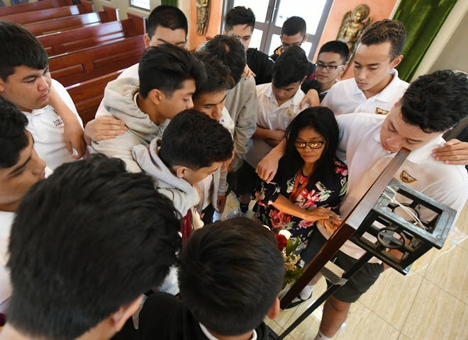 Father Duenas Memorial School students and teacher Jovie Manzanilla gather around a portrait of Xavier Akima, 15, at the conclusion of a prayer service in the school's chapel on Wednesday, Aug. 15, 2018. Akima, an FD student, drowned during a hike to San Carlos Falls.
