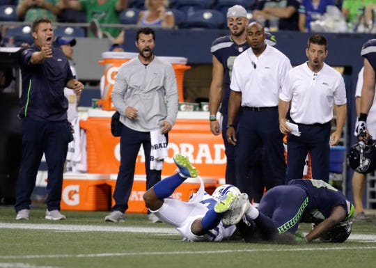 Seattle Seahawks personnel reacted on the sideline after Colts defensive back Shamarko Thomas, lower left, hit Seahawks wide receiver David Moore, lower right, during thier preseason game Aug. 9. Moore was injured on the play; the Colts were penalized 15 yards, and Thomas was ejected. The Colts released Thomas the next day.