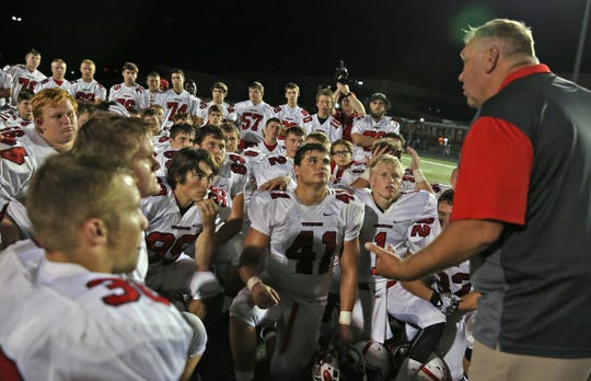 FILE – Center Grove coach Eric Moore talks to his team after beating Lawrence Central, Sept. 25, 2015.