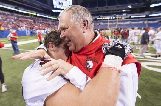 Center Grove's Connor Steeb (32) and coach Eric Moore celebrate winning the IHSAA Class 6A State Championship game, Nov. 28, 2015, at Lucas Oil Stadium.